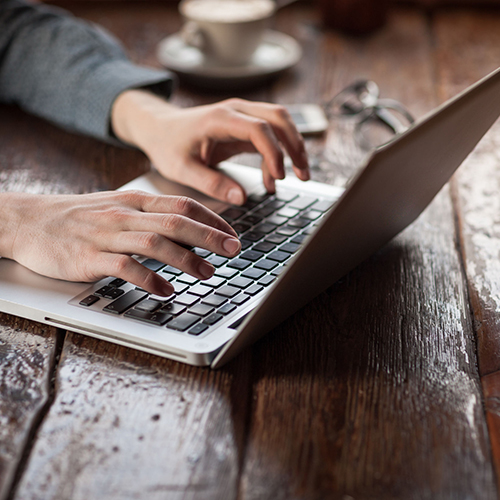 41802185 - man working on a laptop on a rustic wooden table, hands close up